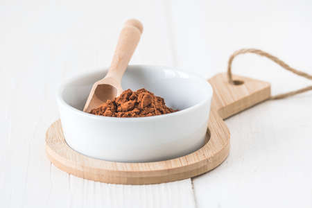 Little bowl with cocoa powder and wooden spoon. Closeup.