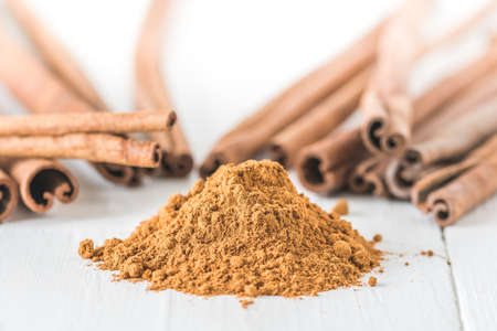 Close-up of cinnamon powder and cinnamon sticks on white wood