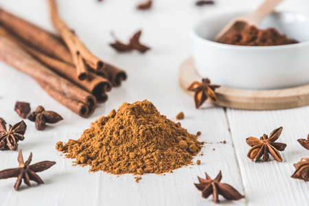 Baking spices like cinnamon, star anise and cocoa on white wooden table