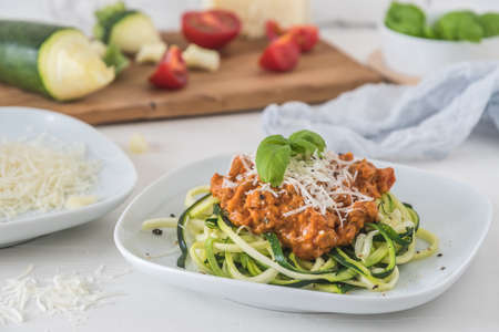 Zoodles bolognese: zucchini noodles with meat or vegan soy meat sauce and parmesan. For low carb, keto, paleo nutrition. 免版税图像