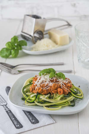 Zoodles bolognese: zucchini noodles with meat or vegan soy meat sauce and parmesan. For low carb, keto, paleo nutrition. Vertical stock photo.