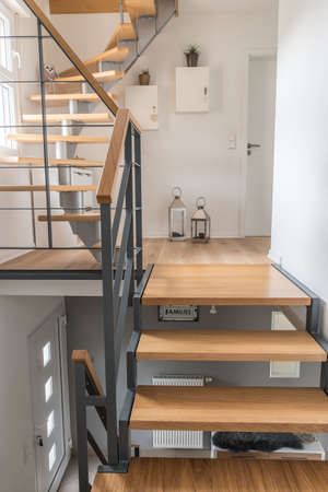 Staircase of a private house with modern stairs. Steel frame with wooden steps, white and gray walls, harmonious color concept. Vertical stock photo.