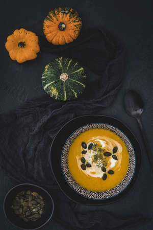 Bowl with pumpkin soup, cream and seeds on black background, decorated with colorful little pumpkins and black cloth and spoon. Vertical stock photo. 免版税图像