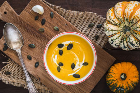 Pumpkin soup with cream and pumpkin seeds on a wooden board on dark brown rustic wooden background, decorated with little pumpkins, spoon and seeds, top view.
