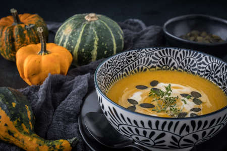 Black-and-white bowl with pumpkin soup, cream and seeds on black background, decorated with colorful little pumpkins and black cloth