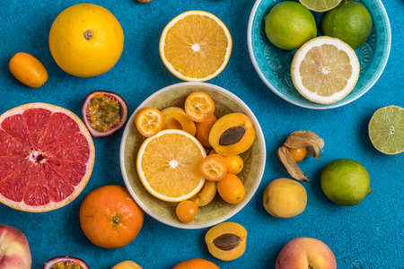c Variety of tropical colorful summer fruits in bowls and on blue background, some of the citrus fruits sliced into halfs
