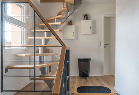 Staircase of a private house with modern stairs. Steel frame with wooden steps, white and gray walls, harmonious color concept.