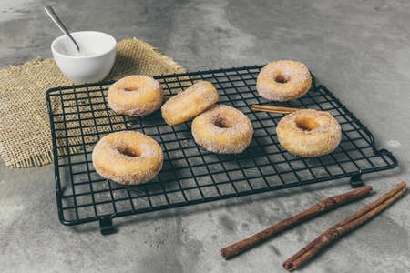 Sugared mini donuts with cinnamon on a cooling rack on a gray background