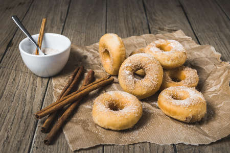 Mini donuts with sugar and cinnamon on a paper on a wooden table