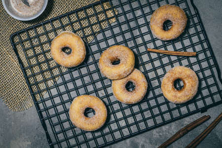 Sugared mini donuts with cinnamon on a cooling rack on a gray background, top view