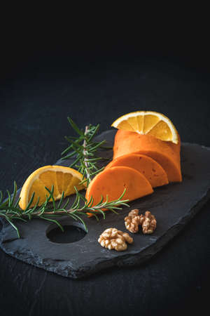 Semicircular piece of orange cheese on a slate, garnished with orange, walnuts and rosemary, vertical with copy space