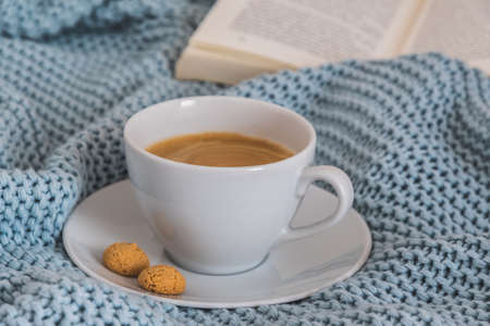 Cup of coffee on a light blue knitted wool blanket. Cozy atmosphere. Coffee break, stay at home concept.