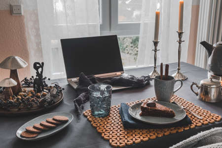 Table with laptop, cake, cookies and autumnal decoration in a cozy room prepared for virtual coffee with family or friends, useful during worldwide pandemic quarantine times Foto de archivo