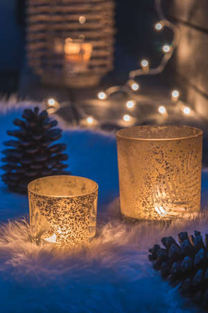 Two decorative glasses with tealights on a lambskin on a veranda in the blue hour, fairy lights and candle light in the background, cozy atmoshpere, vertical stock photo