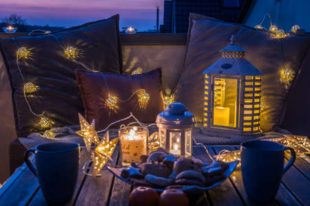 Cozy sitting area with coffee and cookies on a balcony, decorated for winter with lanterns, candles, woolen blankets and fairy lights in beautiful sundown light