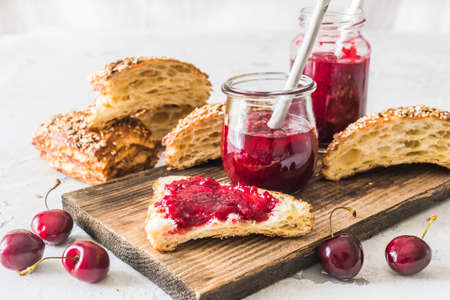 Homemade cherry jam, fresh cherries and cut lye rolls on a wooden board on a white table