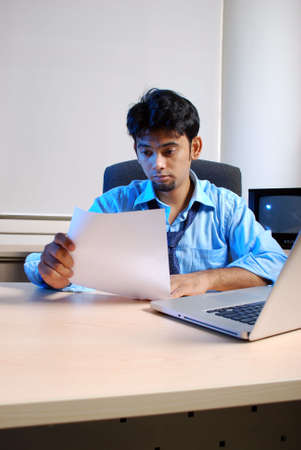 Very gloomy businessman in office environment with laptop. photo