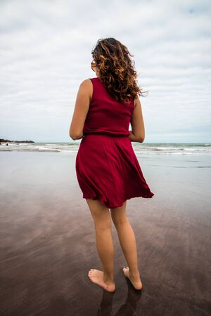 loose hair: Woman on the beach A young woman, standing on the shore of the beach of the port of Veracruz; She is wearing a dark red dress, dark glasses and loose hair. Stock Photo