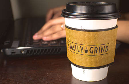 daily grind: Edmonton, Canda, 26 February 2014  A student working on the laptop with a The Daily Grind coffee cup at the side  The Daily Grind is a cafe operated by the students union at the University of Alberta Editorial