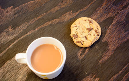 A cup of tea and a chocolate chip cookie kept beside each other