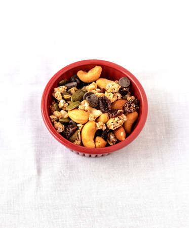 chocolate chips: Trail mix of dry fruits and chocolate chips in a purple coloured bowl