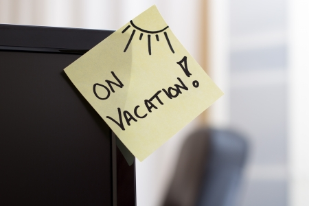 post it note: Note on monitor with text  On vacation