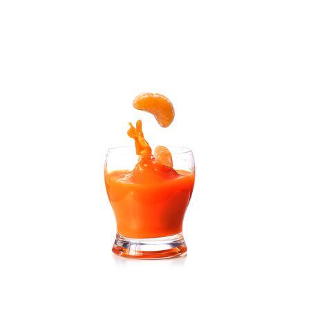 Mandarins falling in glass of juice