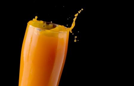 Splashing orange juice in front of black background