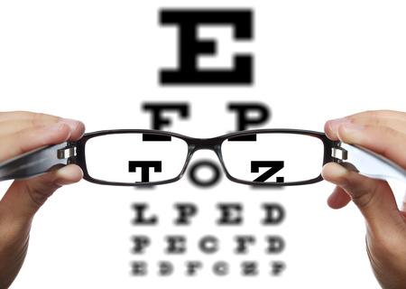 ojos marrones: Gafas en manos delante de examen de la vista