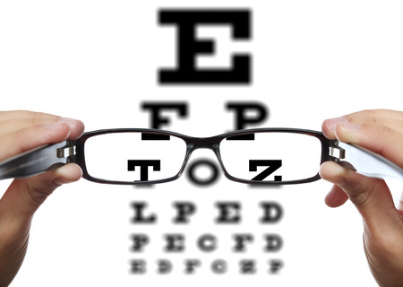 eye exam: Glasses in hands in front of eye test