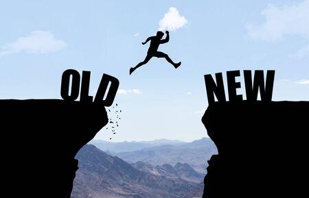 Mann springt über Abgrund mit Text ALT/NEU vor Berghintergrund. Standard-Bild