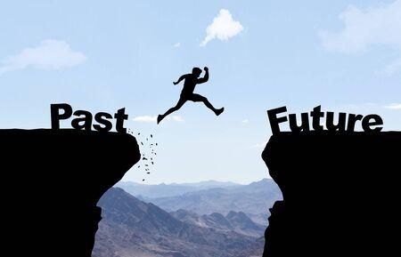 Mann springt über Abgrund mit Text Vergangenheit/Zukunft vor Berghintergrund.
