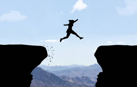 Woman jumping over abyss in front of mountain background.