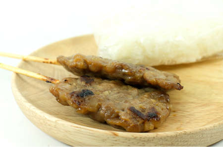 Closeup pork barbecue on wooden dish and white background isolated photo
