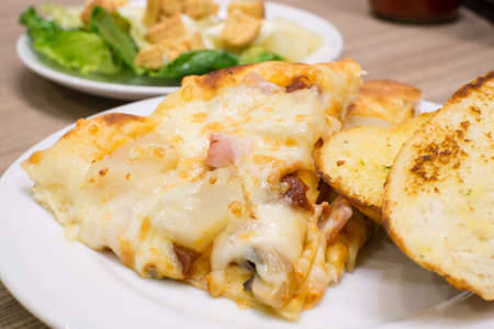 appetising: Closeup view of an appetising ham and pineapple Italian pizza with garlic bread and salad