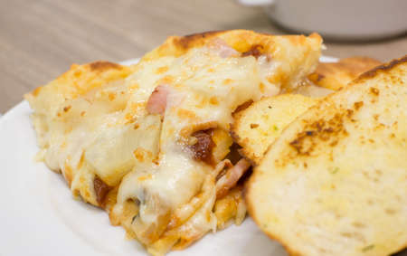 appetising: Closeup view of an appetising ham and pineapple Italian pizza with garlic bread
