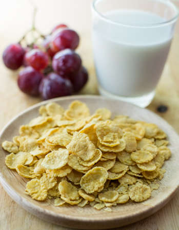 sugarcoated: sugar-coated corn flakes with milk and grape background Stock Photo
