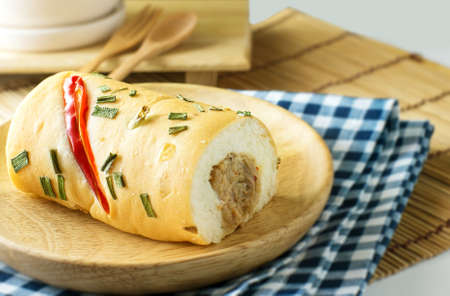 hoagie: tuna bread on wood dish and hot tea in black background