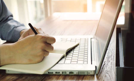 a man is writing some word on notebook with laptop in office room Banque d'images