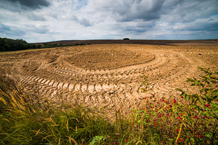 Traces of a tractor on a plowed field. Graphic drawing is not the ground.