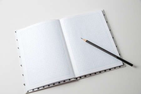 Expanded checkered notebook with open sheets and pencil. Selective focus. Blurred background.