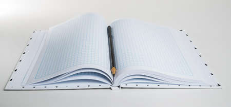 Expanded checkered notebook with open sheets and pencil. Selective focus. Blurred background. Archivio Fotografico