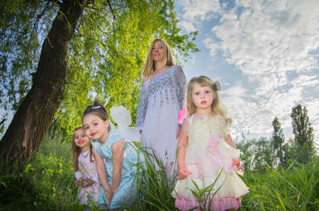 A kind sorceress and little girls elves with wings on a green lawn in the sunlight. Selective focus. Blurred background.