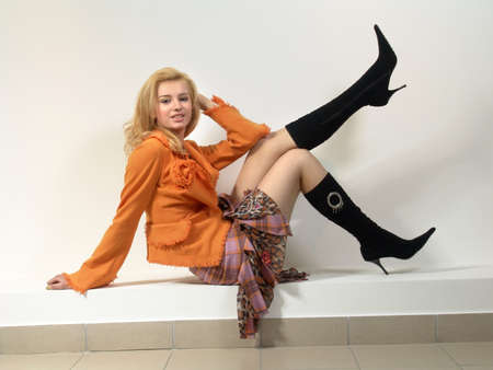 A girl with white hair in black high boots in an orange jacket and a plaid skirt.