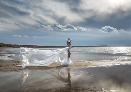 A fabulous girl in a long transparent dress fluttering in the wind and a high headdress on the shore of a reservoir.