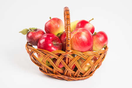 Bright multi-colored fresh apples in a wicker basket on a white background. Selective focus.