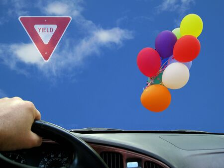 Colorful balloons flying on the blue sky nex to traffic sign
