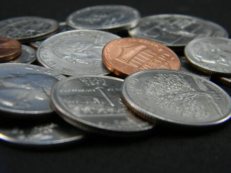 Close-up of coins of dollar, on black background.