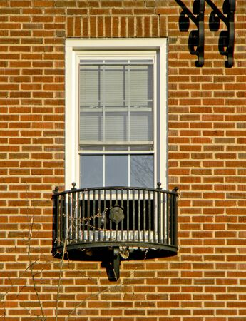White window with balcony  with details in metal, on a wall with orange bricks.