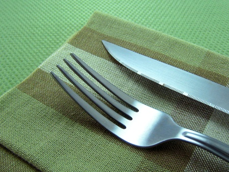 Fork and knife on a dinning table. Stock Photo